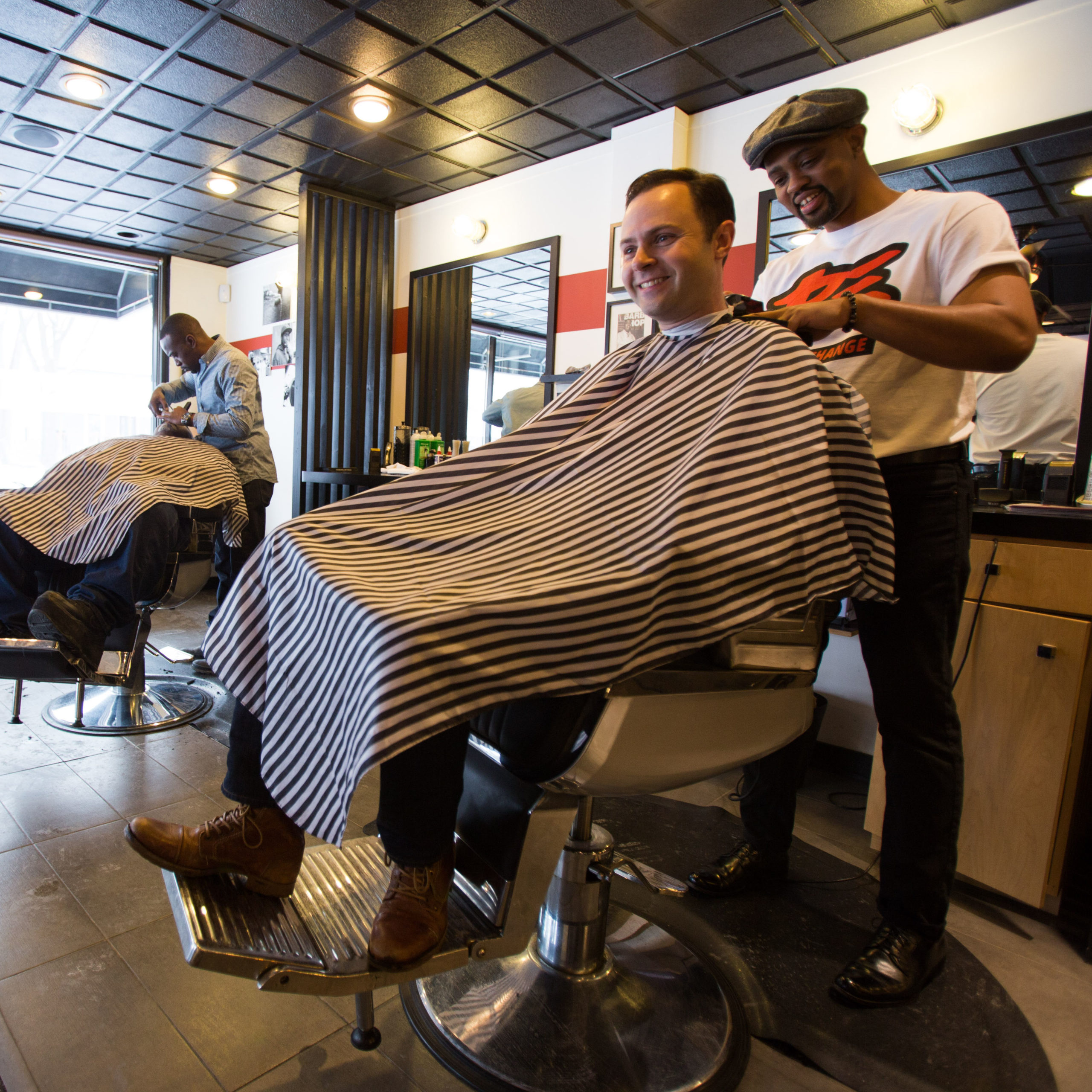 Jake Sturgis, owner of Captivate Media, smiling, getting a haircut in a barbershop.